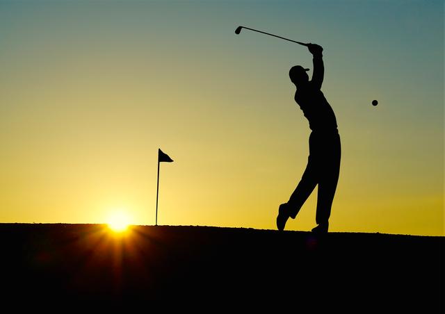 Golfer hitting a golf ball at sunset
