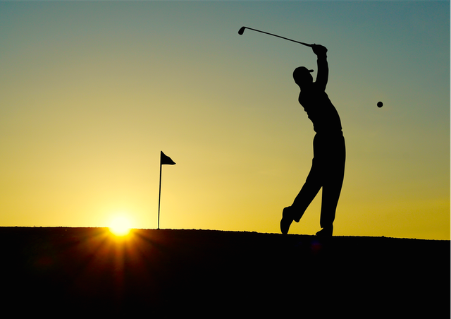 Golfer hitting a golf ball at sunset