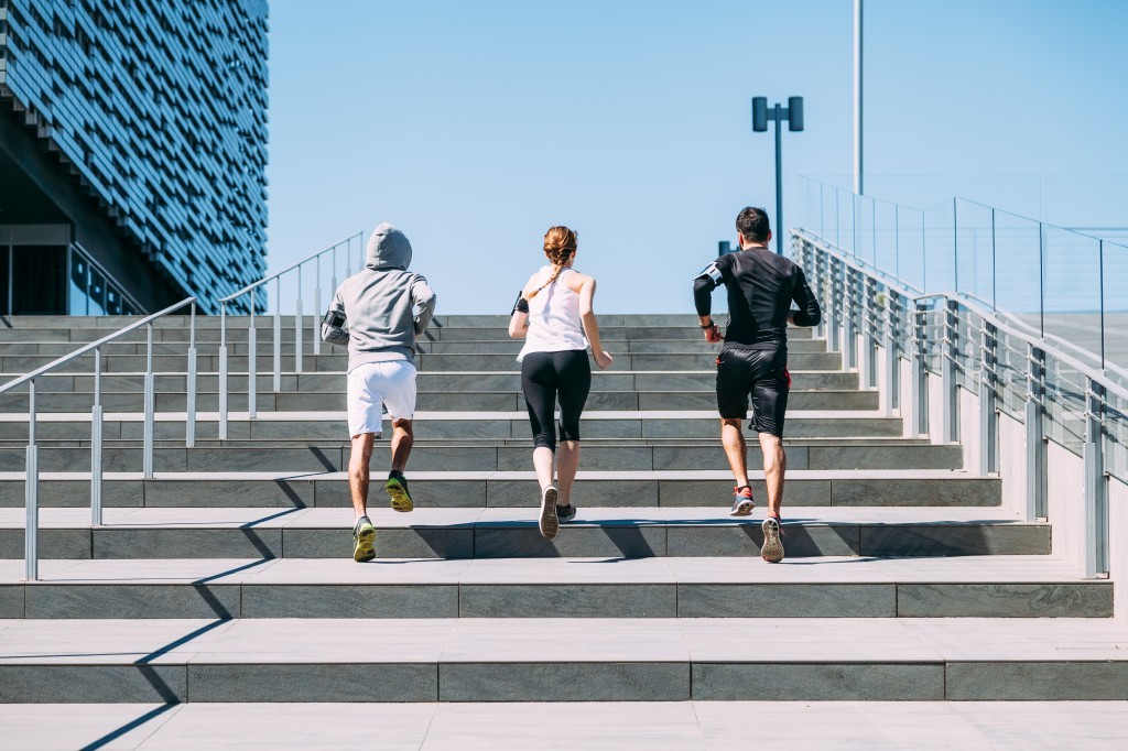 Three young friends running on the steps of a building