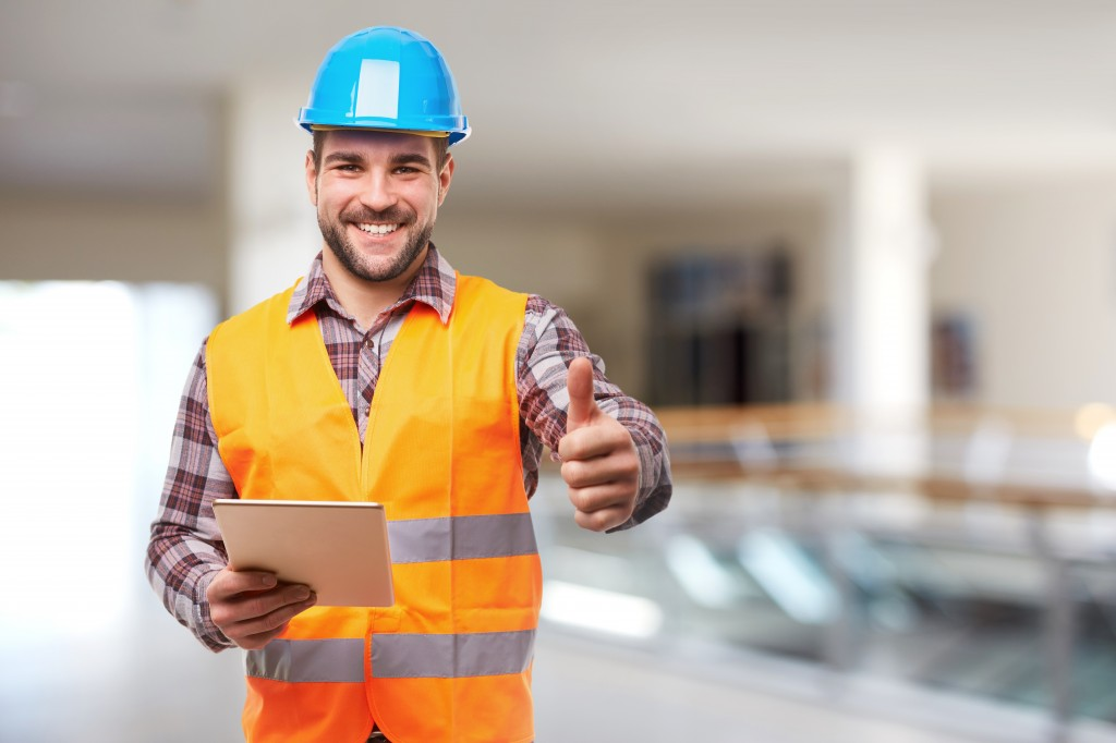 Smiling manual worker in blue helmet gesture thumb up