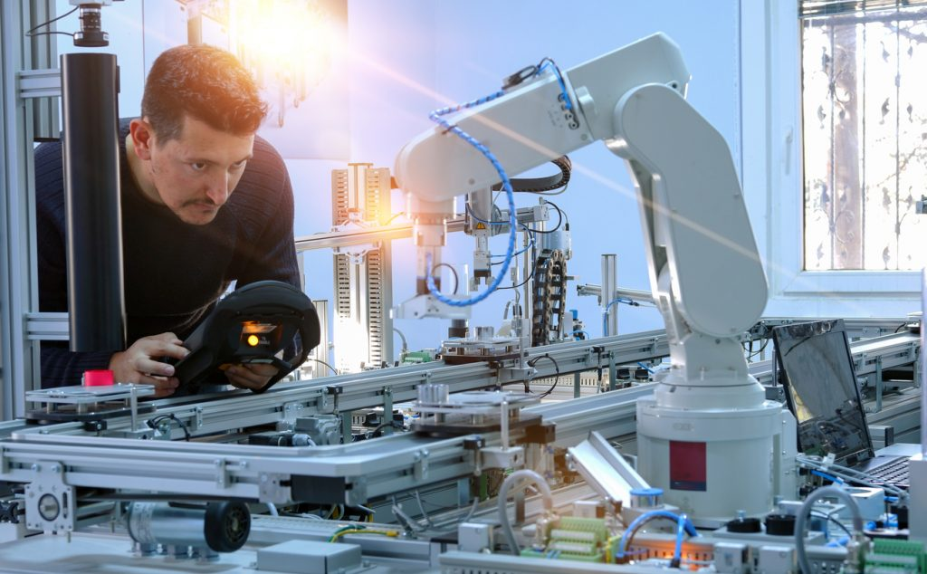 Man is programming robotic arm with control panel which is integrated on smart factory production line. industry 4.0 automation line which is equipped with sensors and robotic arm