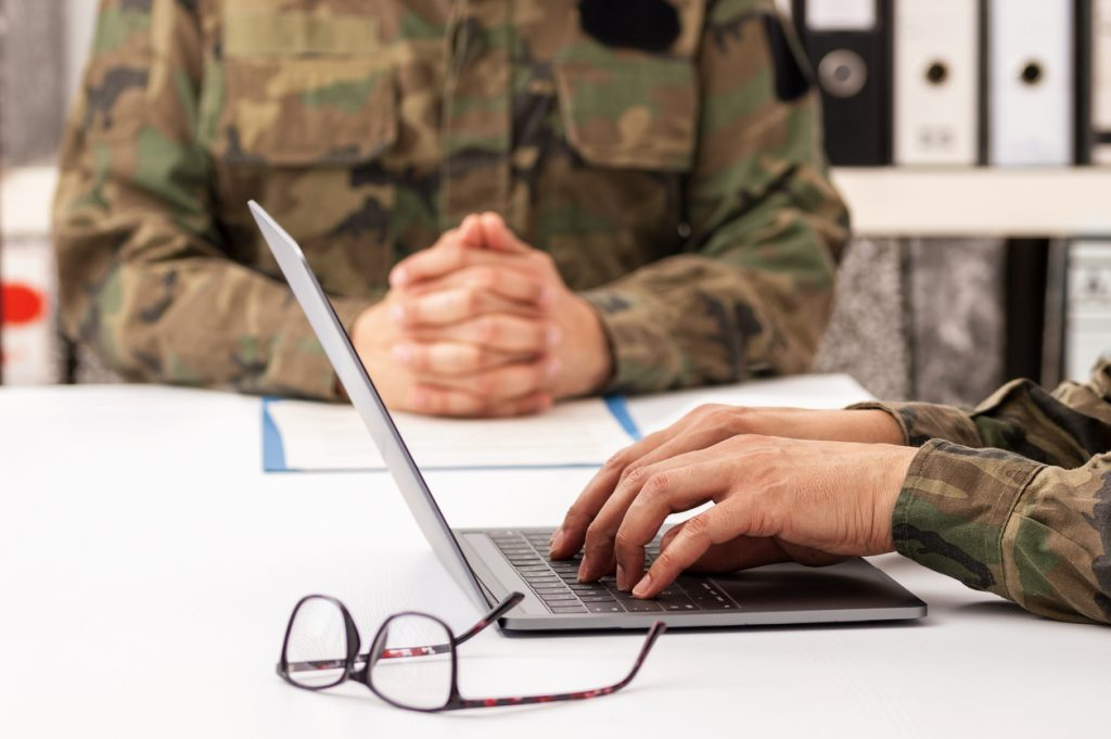 Military officers meet to discuss recruitment. They are using a laptop.