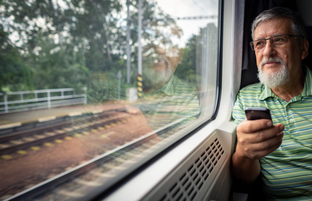 Senior man enjoying a train travel - leaving his car at home, he savours the time spent travelling, looks out of the window, has time to admire the landscape, use his smart phone to catch up with family