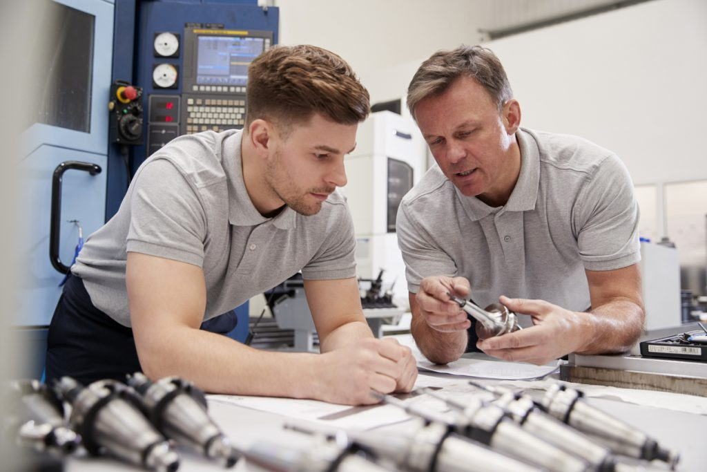Engineer Showing Apprentice How To Measure CAD Drawings